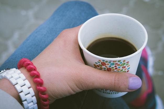 Mädchen in der blue jeans, die den kaffee im freien stillsteht und trinkt Premium Fotos