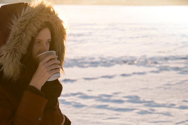 Mädchen in der haube trinkt heißen kaffee am wintertag Premium Fotos