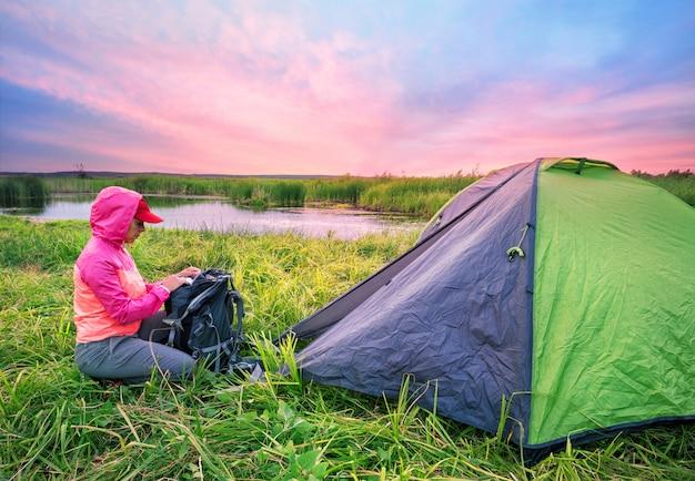 Mädchen in der rosa jacke öffnet ihren rucksack nahe zelt am fluss ba Premium Fotos