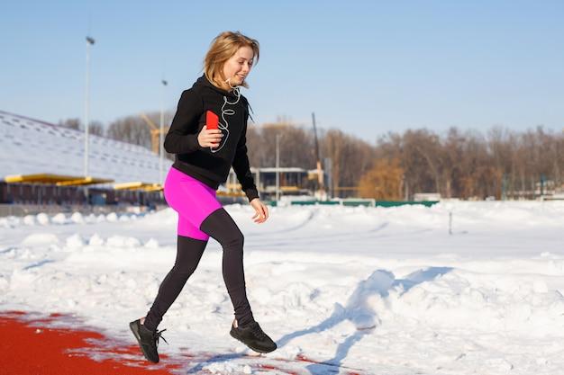 Mädchen in der sportkleidung laufen auf der roten spur für das laufen auf einem schneebedeckten stadion sitz- und sportlebensstil. laufen und musik hören. sport lebensstil Premium Fotos