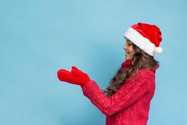 Mädchen in der winterkleidung, die ihre handschuhe betrachtet Kostenlose Fotos