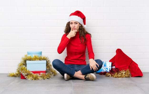 Mädchen in die weihnachtsfeiertage, die auf dem boden denkt eine idee sitzen Premium Fotos