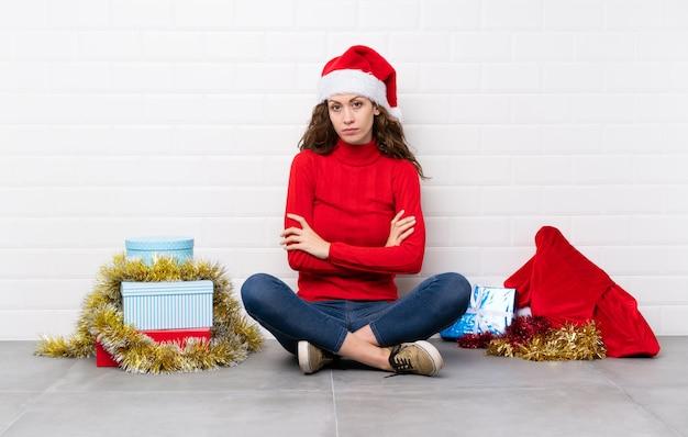 Mädchen in die weihnachtsfeiertage, die auf dem boden hält arme gekreuzt sitzen Premium Fotos