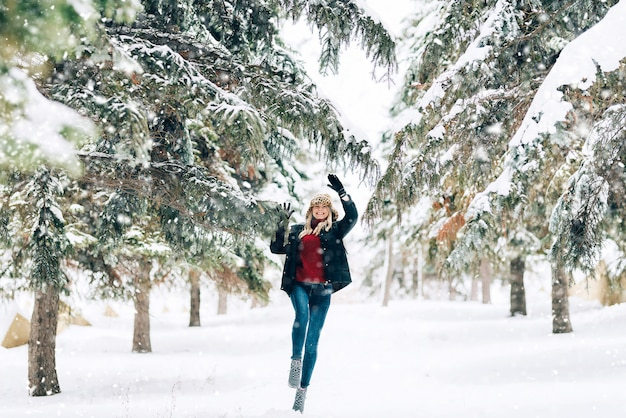 Mädchen in einem modernen winterhut mit einem leoparddruck freut sich im schnee Premium Fotos