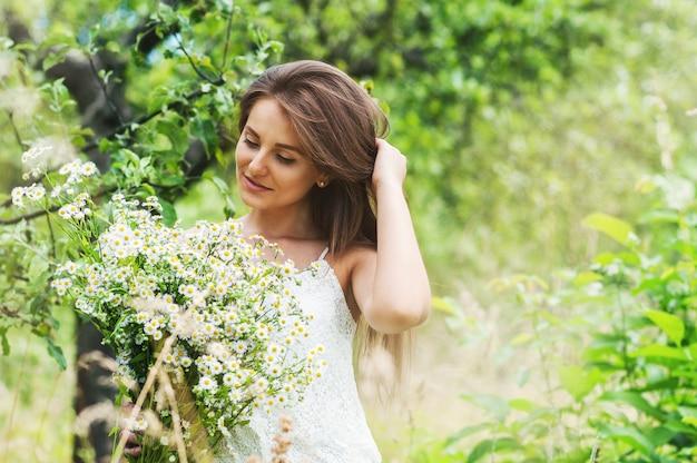 Mädchen in einem weißen kleid, das blumenstrauß und grün hält. Premium Fotos