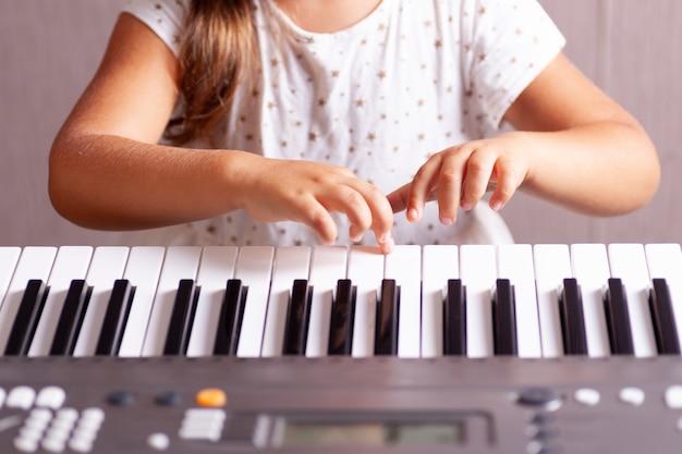 Mädchen in einem weißen kleid, das die tasten eines elektronischen klaviers spielt Premium Fotos