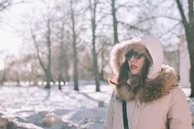 Mädchen in einem winterpark am nachmittag in den schneefällen Premium Fotos