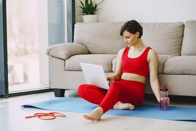 Mädchen in einer roten sportuniform, die yoga zu hause praktiziert Kostenlose Fotos