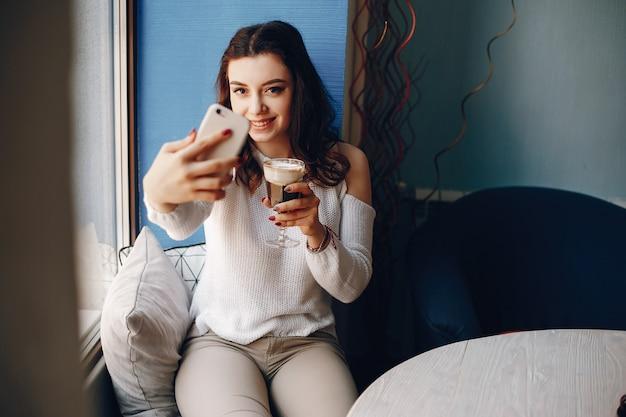 Mädchen in einer weißen strickjacke nimmt ein selfie im café Kostenlose Fotos