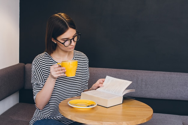 Mädchen in gläsern ein buch in einer kaffeestube lesend Premium Fotos