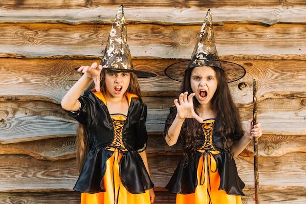 Mädchen in halloween-hexenkostüme, die zauber vortäuschen Kostenlose Fotos