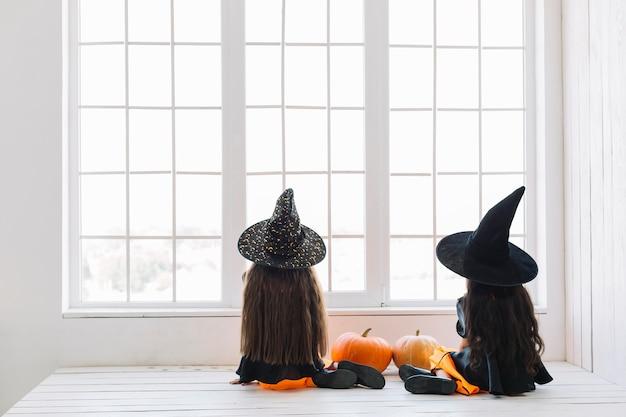 Mädchen in halloween-kostümen, die nahe fenster sitzen Kostenlose Fotos