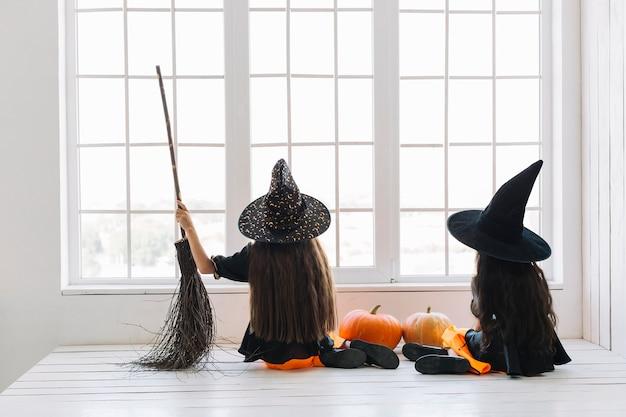 Mädchen in halloween-kostümen mit dem besen, der nahe fenster sitzt Kostenlose Fotos