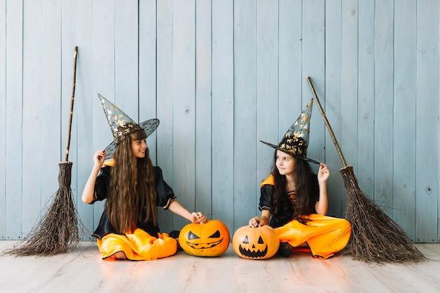 Mädchen in halloween-kostümen mit spitzen hüten und besen sitzen am zaun Kostenlose Fotos
