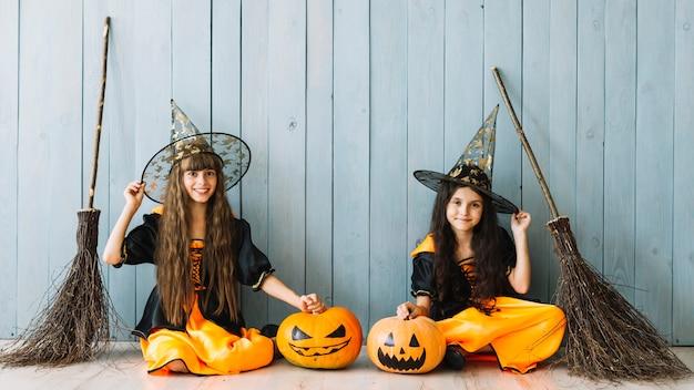 Mädchen in hexenkostümen, die mit kürbisen und besen sitzen Kostenlose Fotos