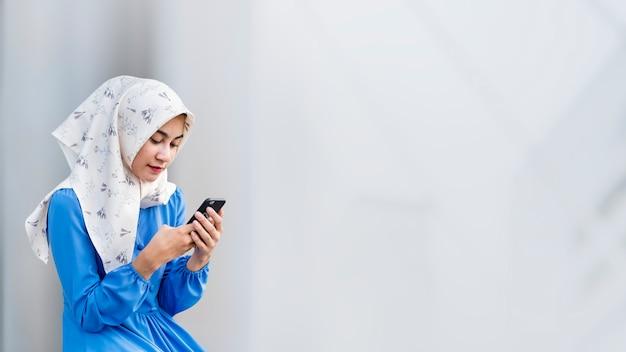 Mädchen in hijab mit einem telefon Premium Fotos