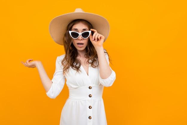 Mädchen in hut und brille sie ein weißes kleid auf einem gelben Premium Fotos