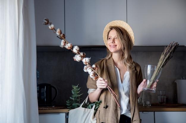Mädchen in jacke mit einkaufstasche und baumwollpflanze in einer küche Premium Fotos