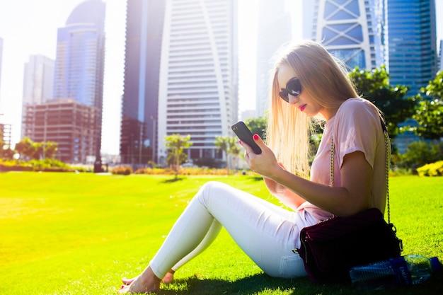 Mädchen in rosa hemd und weiße jeans überprüft ihr telefon sitzt auf dem rasen im park Kostenlose Fotos