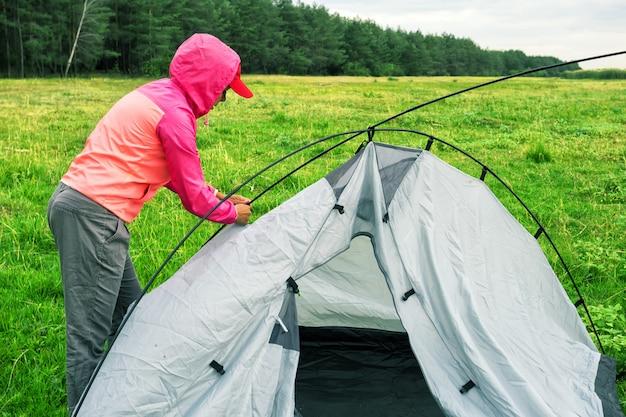 Mädchen in rosa jacke und mütze sammelt zelt auf grünem feld Premium Fotos