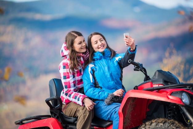 Mädchen in winterjacken auf rotem atv Premium Fotos