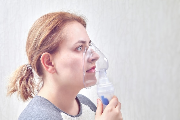 Mädchen inhaliert medizin durch gerät zum einatmen vernebeln, es hilft, asthmaanfall zu stoppen. Premium Fotos