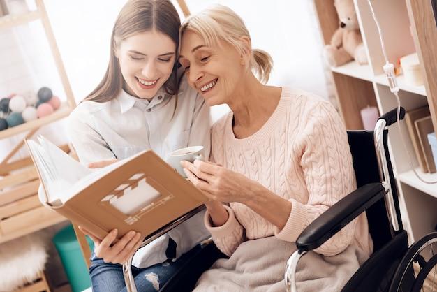 Mädchen interessiert sich für ältere frau im rollstuhl zu hause. Premium Fotos