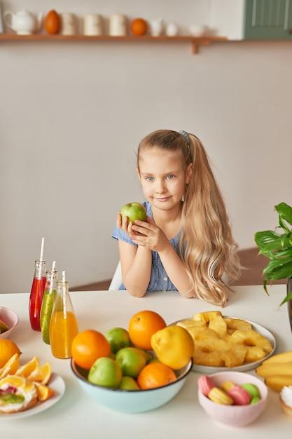Mädchen isst obst auf einem tisch voller essen Premium Fotos