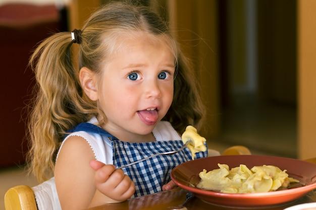 Mädchen isst pasta Premium Fotos