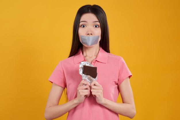 Mädchen ist kann die schokolade nicht essen, die auf gelb lokalisiert wird. Premium Fotos
