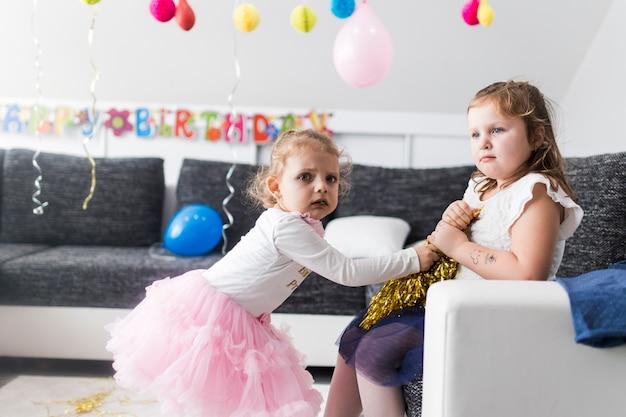 Mädchen kämpfen für lametta auf party | Kostenlose Foto