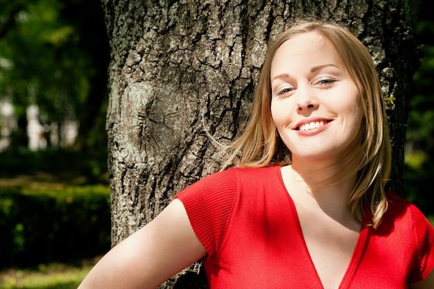 Mädchen lächelnd mit einem baum im rücken Premium Fotos