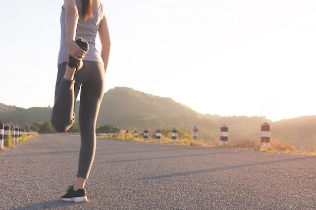 Mädchen läufer vor dem laufen auf der straße aufwärmen Premium Fotos