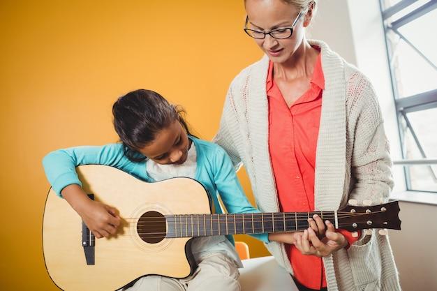 Mädchen lernen, wie man gitarre spielt Premium Fotos