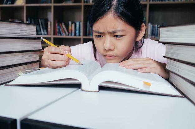 Mädchen lesen und schreiben und hausaufgaben in der bibliothek Premium Fotos