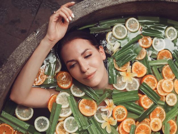 Mädchen liegt in einem runden bad mit früchten Kostenlose Fotos
