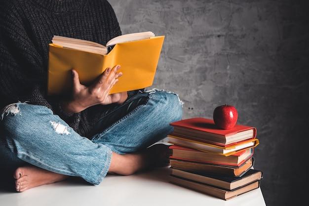 Mädchen liest bücher, studiert, entwickelt auf einem weißen tisch und einem grauen hintergrund. Premium Fotos