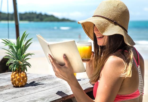 Mädchen liest ein buch am meer Kostenlose Fotos
