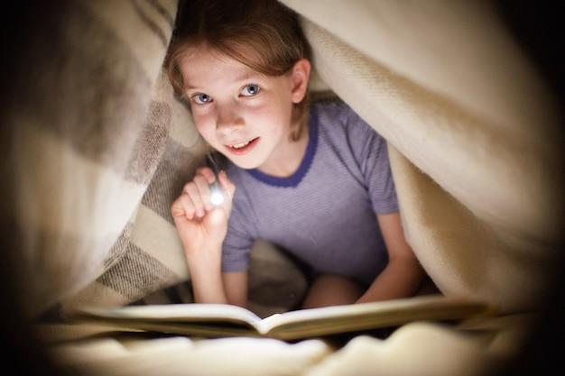 Mädchen liest ein buch unter einer decke mit einer taschenlampe in einem dunklen raum nachts Premium Fotos