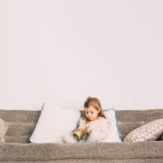 Mädchen liest magazin auf der couch Kostenlose Fotos