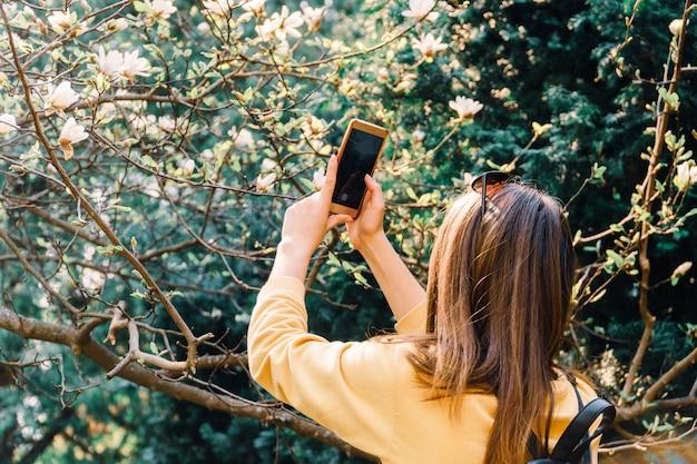 Mädchen macht foto von magniloa-blume auf der smartphone-kamera. sozialen medien Premium Fotos