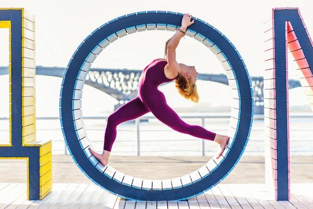 Mädchen macht yoga in einem ring am strand Premium Fotos