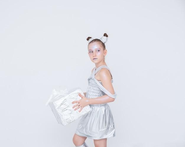 Mädchen mädchen mit schwänzen hörner in einem silbernen kleid hält eine geschenkbox Premium Fotos