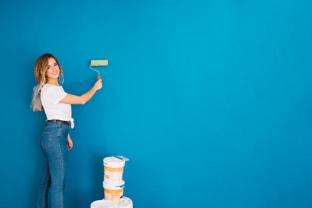 Mädchen malt wand mit rolle Kostenlose Fotos