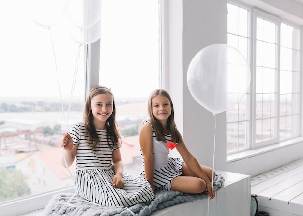 Mädchen mit ballonen nahe fenster Kostenlose Fotos
