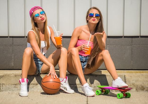 Mädchen mit basketball und skateboard und trinkendem saft. Premium Fotos