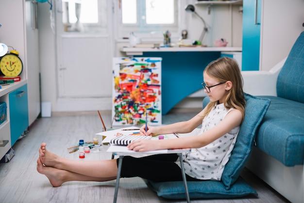 Mädchen mit bleistift bei tisch im raum mit wasserfarben auf boden malen Kostenlose Fotos