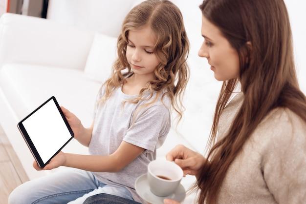 Mädchen mit brauner haarmutter wählen frisur auf tablette. Premium Fotos
