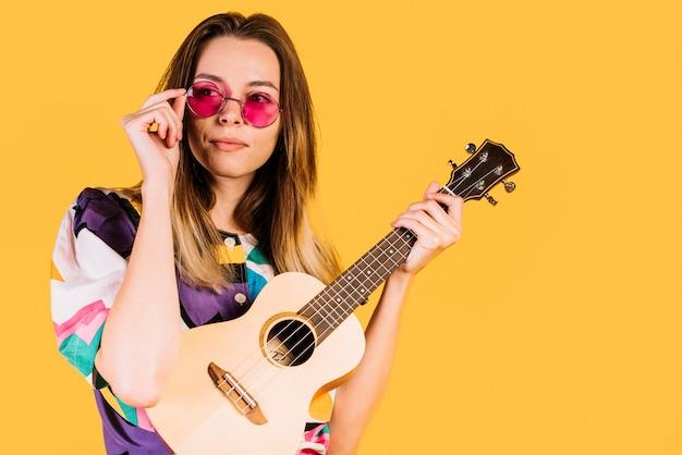 Mädchen mit brille mit einem ukulele Kostenlose Fotos