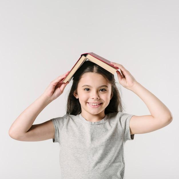 Mädchen mit buch auf kopf im studio Kostenlose Fotos